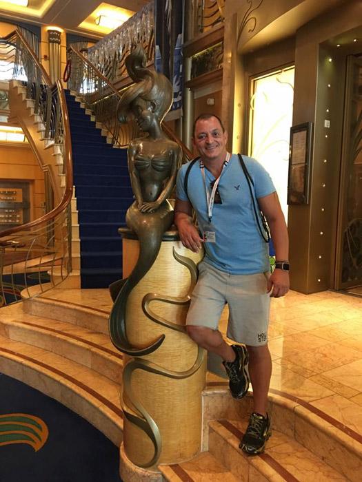 Hernani com a estátua da Ariel no lobby do Disney Wonder