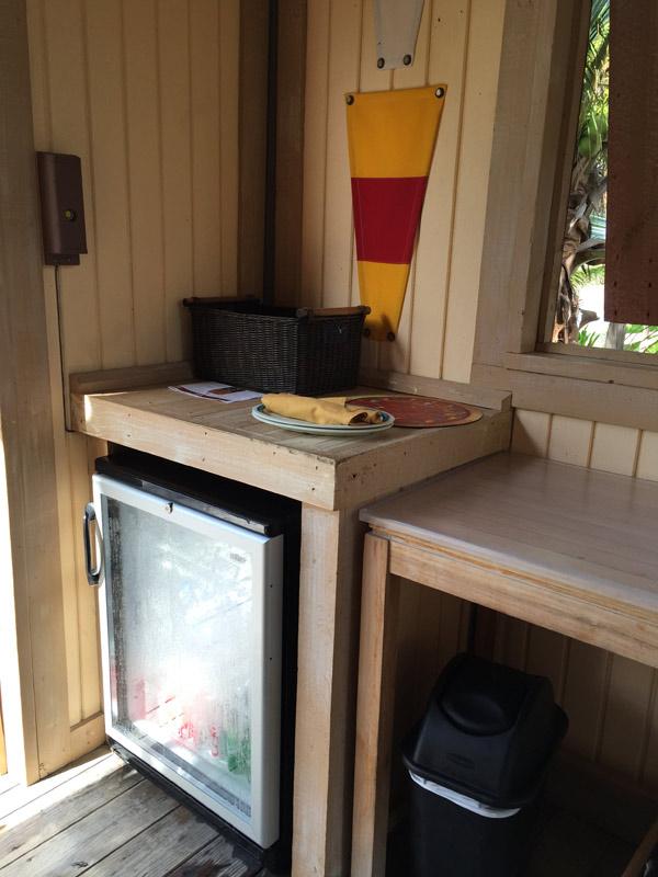 A bancada com geladeira, cesta com alguns salgadinhos, pratos e o menu