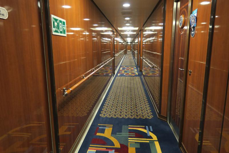 O corredor das cabines Concierge é diferente dos demais, com acabamento em madeira